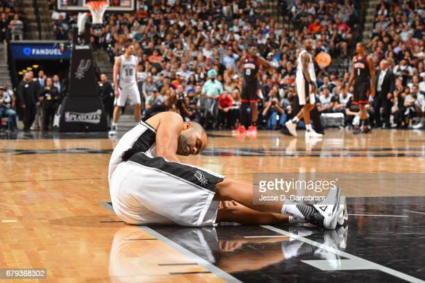 Tony Parker of the San Antonio Spurs holds his knee after sustaining an injury during Game Two of the Western Conference Semifinals against the...