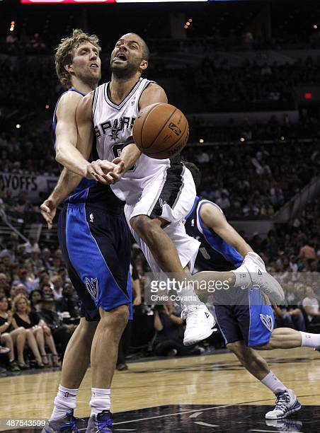 Tony Parker of the San Antonio Spurs is fouled in the lane by Dirk Nowitzki of the Dallas Mavericks in Game Five of the Western Conference...
