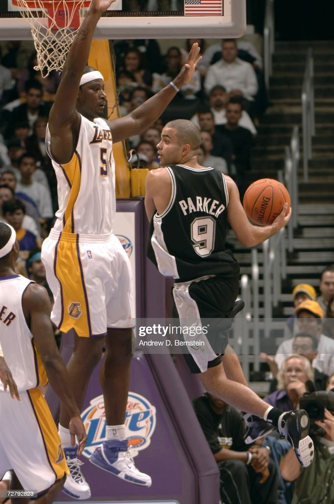 Tony Parker #9 of the San Antonio Spurs looks to pass the ball against Kwame Brown #54 of the Los Angeles Lakers at Staples Center December 10, 2006 in Los Angeles, California.