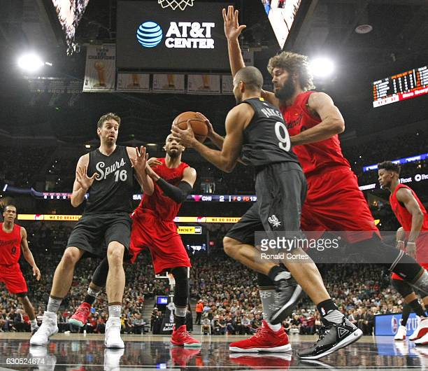 Tony Parker of the San Antonio Spurs looks to pass to Pau Gasol of the San Antonio Spurs as he is guarded by Robin Lopez of the Chicago Bulls at ATT...