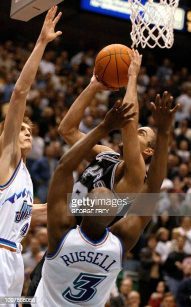 Tony Parker of the San Antonio Spurs makes the gamewinning shot as Brian Russell and Andrei Kirilenko of the Utah Jazz defend 17 April 2002 in Salt...