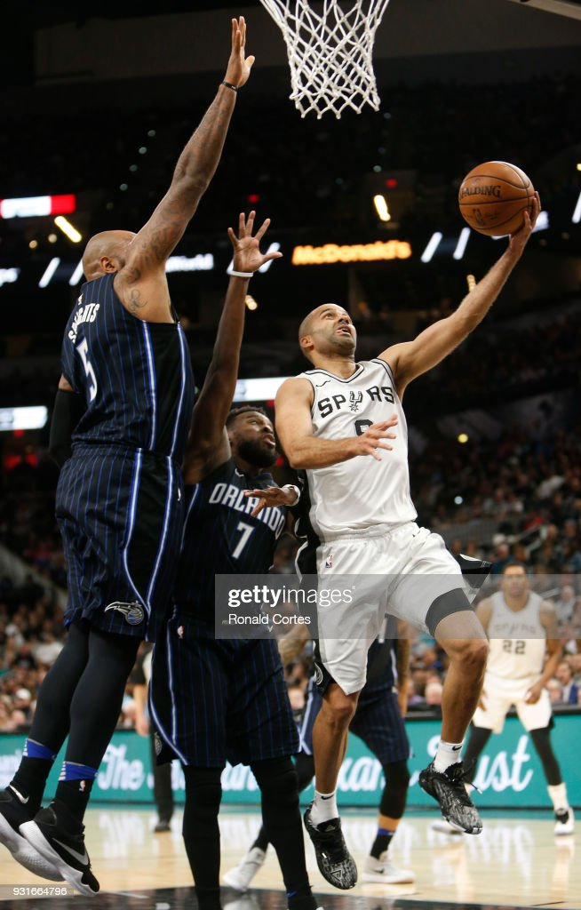 Tony Parker #9 of the San Antonio Spurs scores past Shelvin Mack #7 and Marreese Speights #5 of the Orlando Magic of the Orlando Magic at AT&T Center on March 13, 2018 in San Antonio, Texas.