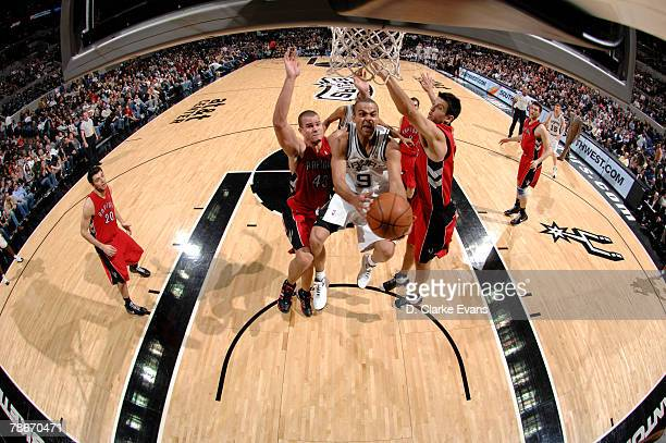 Tony Parker of the San Antonio Spurs shoots against Kris Humphries and Jason Kapono of the Toronto Raptors at the ATT Center December 28 2007 in San...