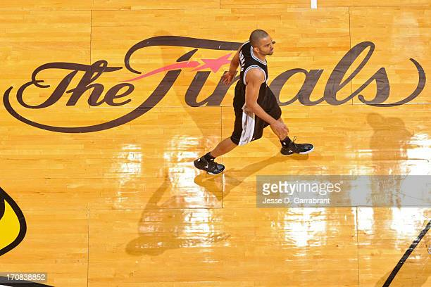 Tony Parker of the San Antonio Spurs walks past The Finals logo on court while playing the Miami Heat during Game Six of the 2013 NBA Finals on June...
