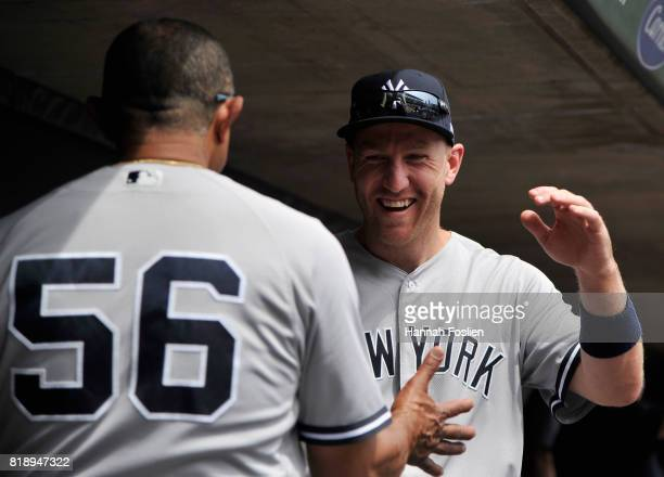 Tony Pena of the New York Yankees welcomes Todd Frazier to the dugout during the second inning of the game against the Minnesota Twins on July 19...