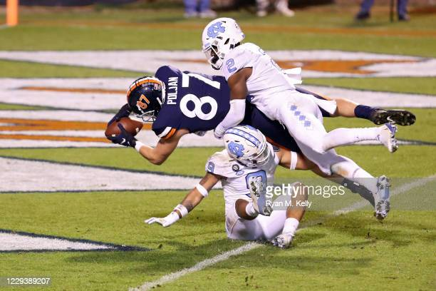 Tony Poljan of the Virginia Cavaliers scores a touchdown between Don Chapman and Cam'Ron Kelly of the North Carolina Tar Heels in the second half...