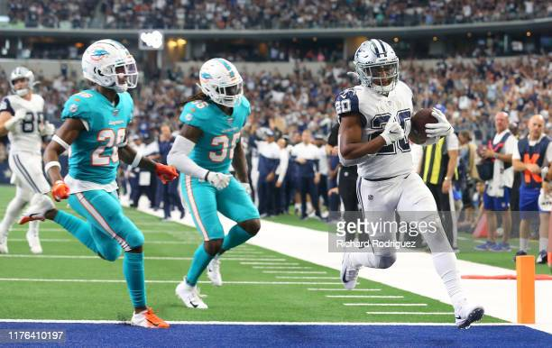 Tony Pollard of the Dallas Cowboys scores a touchdown ahead of Steven Parker and Walt Aikens of the Miami Dolphins in the fourth quarter at AT&T...