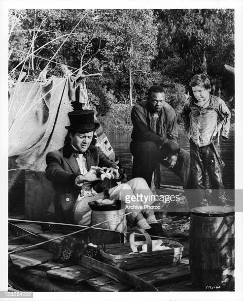 Tony Randall hops a ride on Archie Moore and Eddie Hodges' raft in a scene from the film 'The Adventures Of Huckleberry Finn' 1960