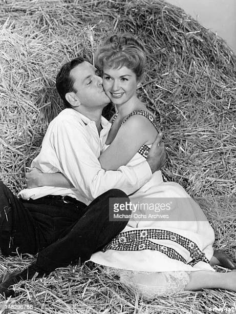 Tony Randall is kissing Debbie Reynolds on the cheek as snuggle up in a haystack together in a scene from the film 'The Mating Game' 1959