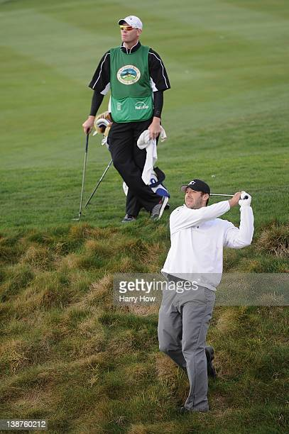 Tony Romo NFL football quarterback for the Dallas Cowboys hits a shot on the ninth hole as his caddie looks on during the third round of the ATT...