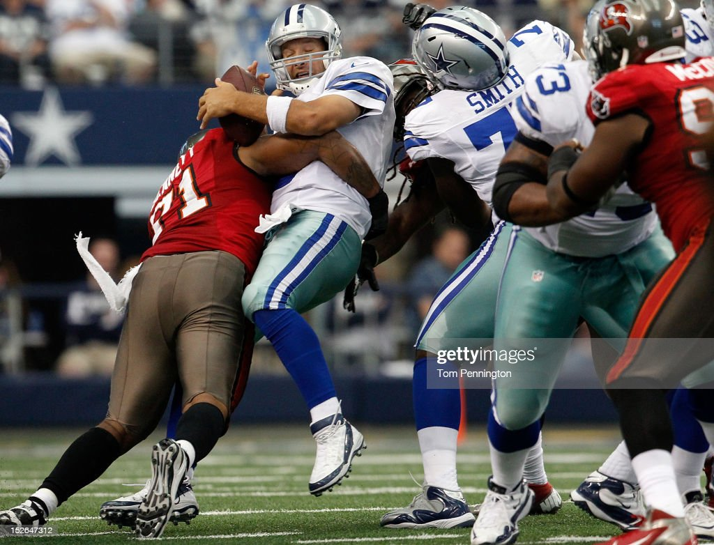 Tony Romo #9 of the Dallas Cowboys fumbles the ball after being hit by Michael Bennett #71 of the Tampa Bay Buccaneers at Cowboys Stadium on September 23, 2012 in Arlington, Texas. The Dallas Cowboys beat the Tampa Bay Buccaneers 16-10.
