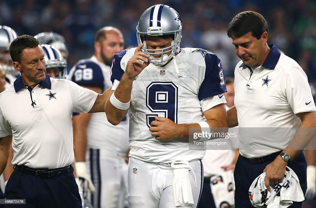 Tony Romo #9 of the Dallas Cowboys is looked after by team officials after being sacked by the Carolina Panthers in the third quarter at AT&T Stadium on November 26, 2015 in Arlington, Texas. Romo left the field following the play.