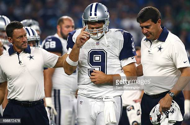 Tony Romo of the Dallas Cowboys is looked after by team officials after being sacked by the Carolina Panthers in the third quarter at ATT Stadium on...