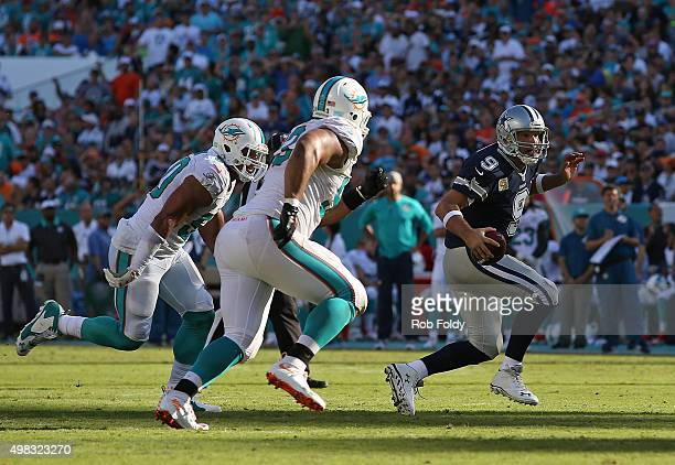 Tony Romo of the Dallas Cowboys is pressured by Olivier Vernon and Ndamukong Suh of the Miami Dolphins before being sacked during the second half of...
