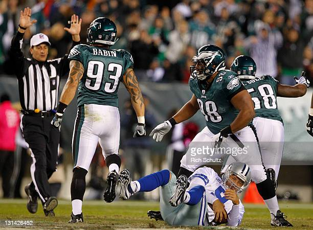 Tony Romo of the Dallas Cowboys is sacked by Jason Babin and Marcus Spears of the Philadelphia Eagles during a game at Lincoln Financial Field on...