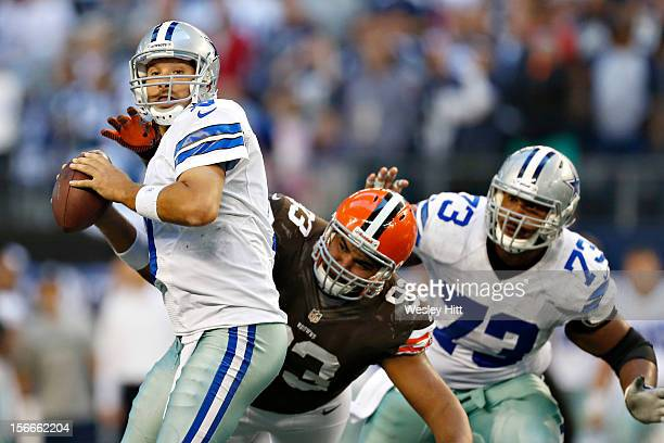 Tony Romo of the Dallas Cowboys looks downfield for a receiver under pressure from John Hughes of the Cleveland Browns at Cowboys Stadium on November...