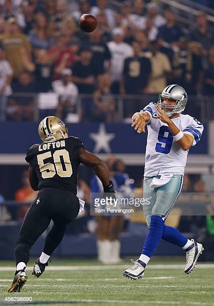 Tony Romo of the Dallas Cowboys passes as Curtis Lofton of the New Orleans Saints rushes in the first half at ATT Stadium on September 28 2014 in...