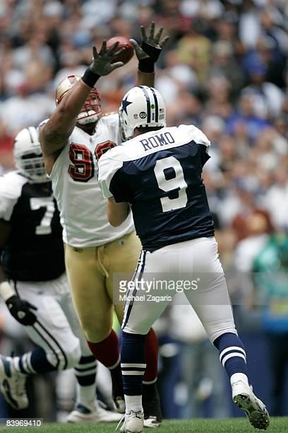 Tony Romo of the Dallas Cowboys passes the ball under pressure during an NFL football game against the San Francisco 49ers at Texas Stadium on...