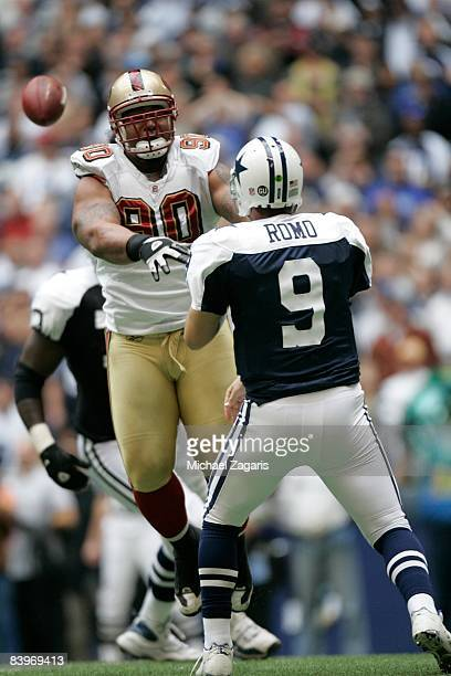Tony Romo of the Dallas Cowboys passes the ball under pressure from Isaac Sopoaga he San Francisco 49ers during an NFL football game at Texas Stadium...