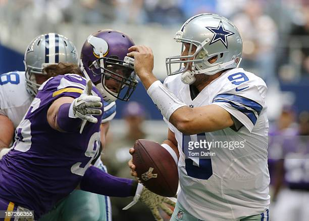 Tony Romo of the Dallas Cowboys scrambles as he is pursued by Brian Robison of the Minnesota Vikings during an NFL game against the Minnesota Vikings...