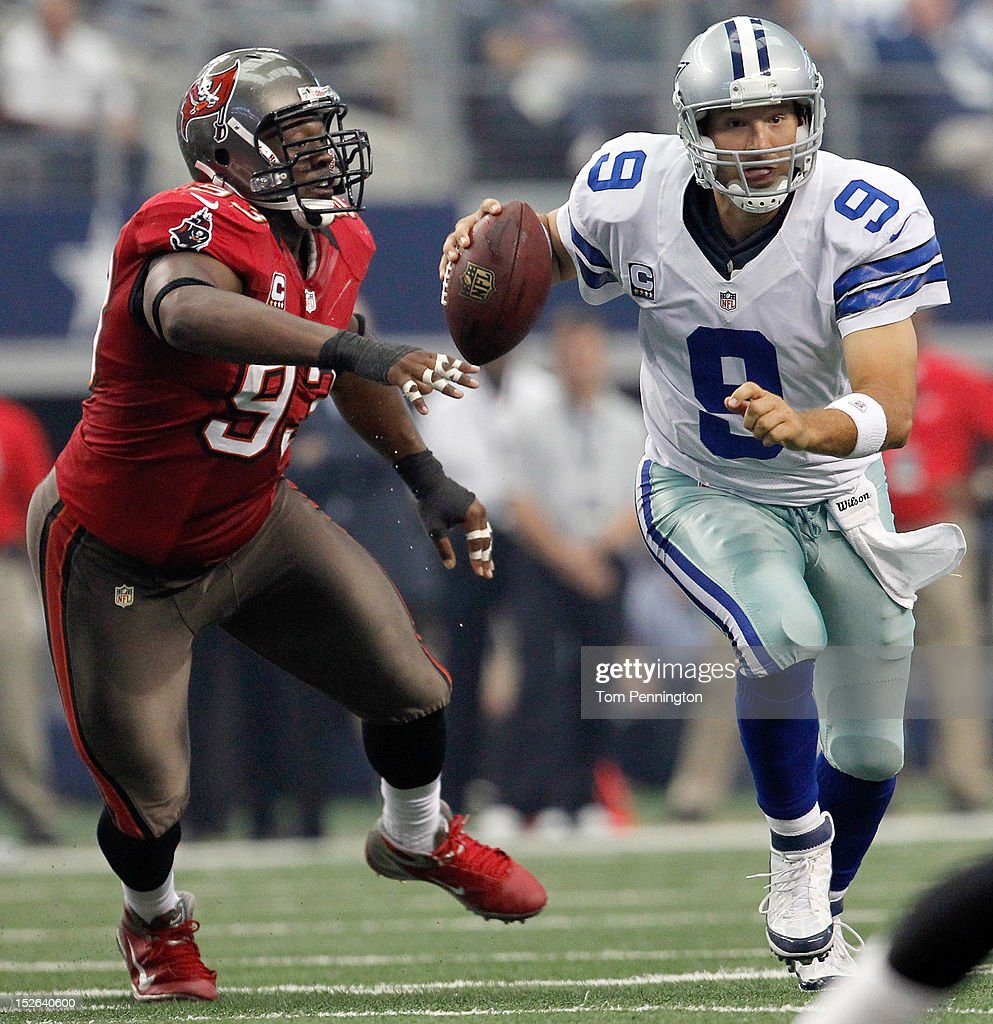Tony Romo #9 of the Dallas Cowboys scrambles with the ball against Gerald McCoy #93 of the Tampa Bay Buccaneers at Cowboys Stadium on September 23, 2012 in Arlington, Texas.