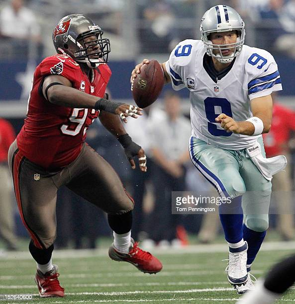 Tony Romo of the Dallas Cowboys scrambles with the ball against Gerald McCoy of the Tampa Bay Buccaneers at Cowboys Stadium on September 23 2012 in...