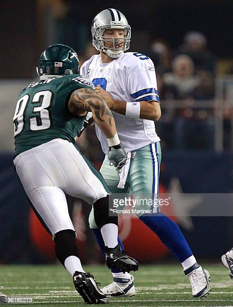 Tony Romo of the Dallas Cowboys suffers a right hand injury after a tackle by Jason Babin of the Philadelphia Eagles at Cowboys Stadium on December...