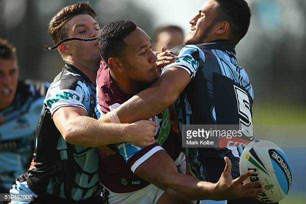 Tony Satini of the Eagles passes as he is tackled during the NRL Trial match between the Cronulla Sharks and the Manly Sea Eagles at Remondis Stadium...