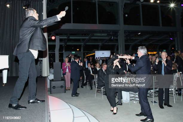 Tony Scotti and Sylvie Vartan sitting Sidney Toledano dancing with Marie Drucker as Singer Julien Clerc performs during the Gala evening of the...