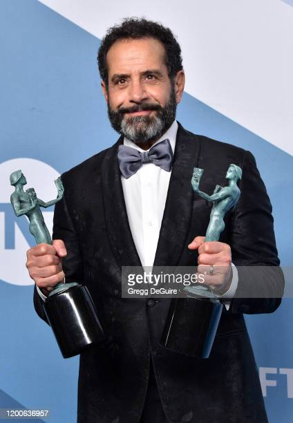 Tony Shalhoub poses in the press room with the trophies for Outstanding Performance by a Male Actor in a Comedy Series and Outstanding Performance by...