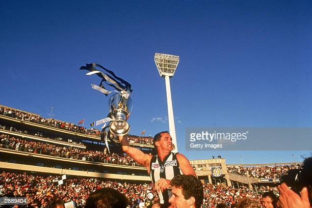 Tony Shaw captain of the Magpies celebrates with the Premiership trophy after winning the 1990 AFL Grand Final played between the Collingwood Magpies...