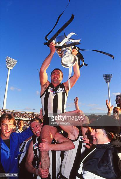 Tony Shaw of the Magpies celebrates with the Premiership trophy after winning the VFL Grand Final between Collingwood Magpies and Essendon Bombers at...