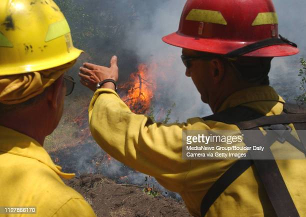 Tony Simons, right, of Larimer County, talks to another firefighter about the progress of the fire in Big Elk Meadows on Sunday.