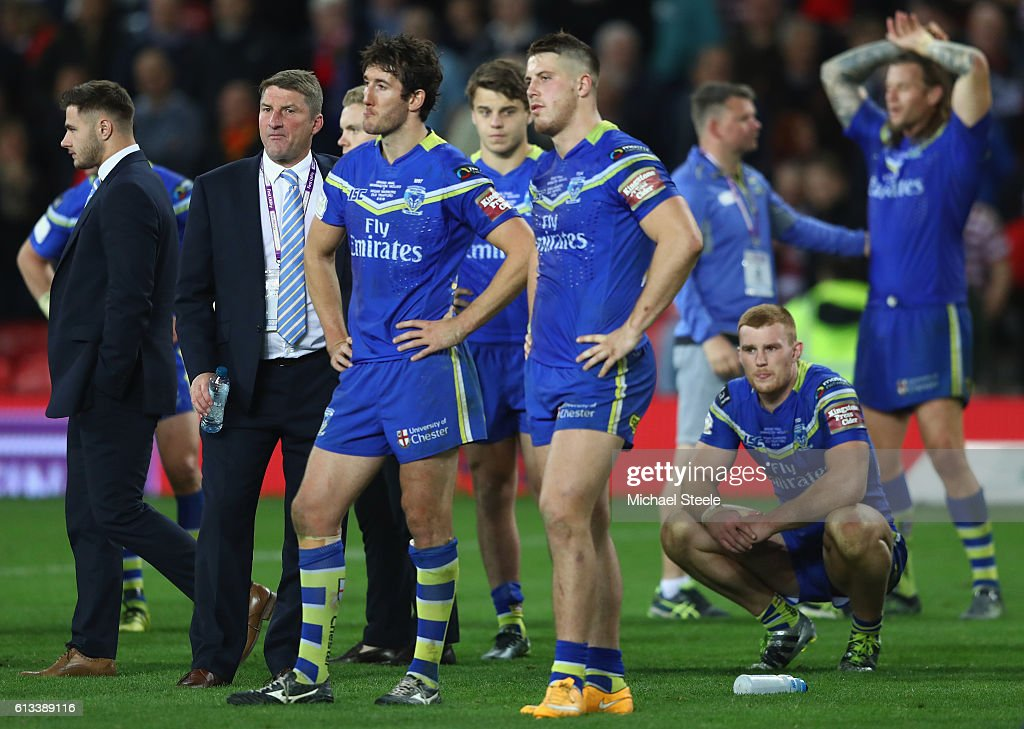 Tony Smith (2L) the coach of Warrington looks on alongside dejected players after his sides 6-12 defeat during the First Utility Super League Final between Warrington Wolves and Wigan Warriors at Old Trafford on October 8, 2016 in Manchester, England.