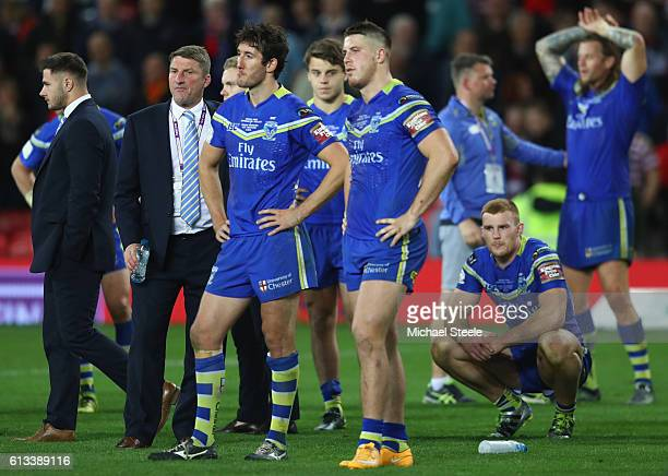 Tony Smith the coach of Warrington looks on alongside dejected players after his sides 612 defeat during the First Utility Super League Final between...