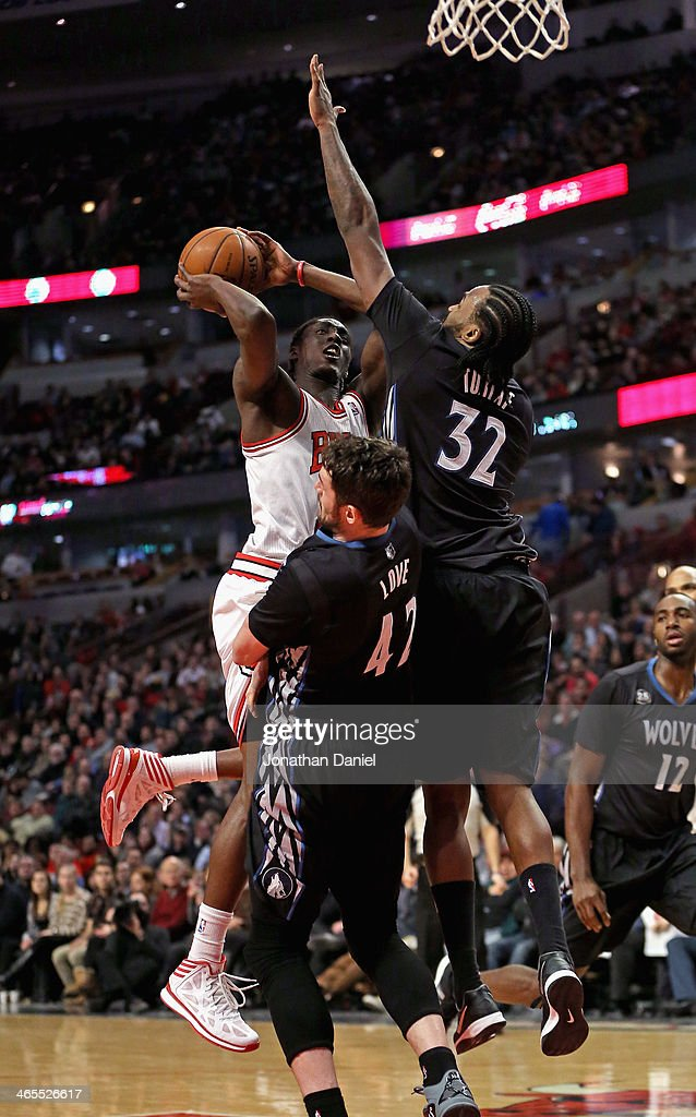 Tony Snell #20 of the Chicago Bulls charges into Kevin Love #42 and Ronny Turiaf #32 of the Minnesota Timberwolves at the United Center on January 27, 2014 in Chicago, Illinois. The Timberwolves defeated the Bulls 95-86.