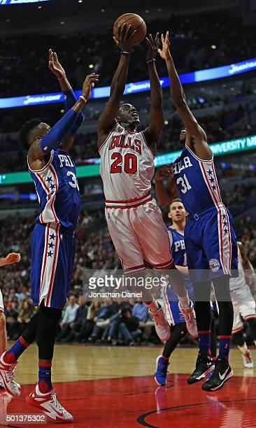 Tony Snell of the Chicago Bulls gets off a shot between Robert Covington and Hollis Thompson of the Philadelphia 76ers at the United Center on...