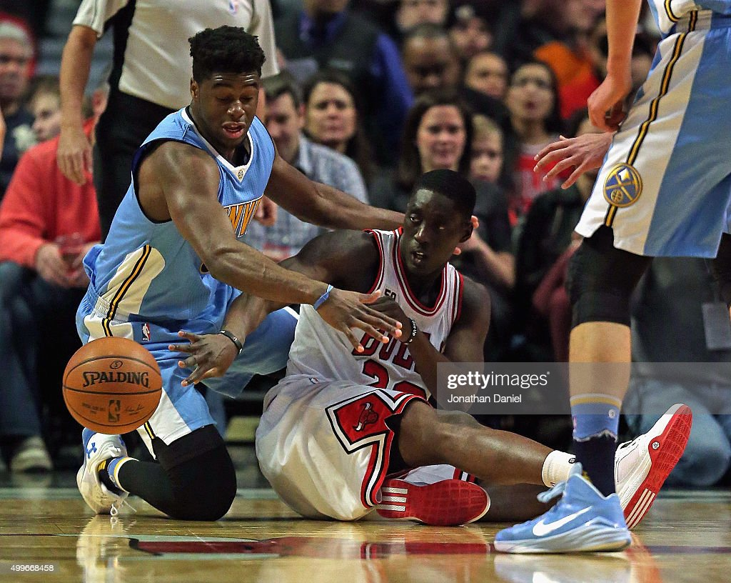 Tony Snell #20 of the Chicago Bulls passes the ball from the floor under pressure from Emmanuel Mudiay #0 of the Denver Nuggets at the United Center on December 2, 2015 in Chicago, Illinois. Note to User: User expressly acknowledges and agrees that, by downloading and or using the photograph, User is consenting to the terms and conditions of the Getty Images License Agreement.