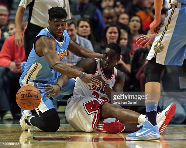 Tony Snell of the Chicago Bulls passes the ball from the floor under pressure from Emmanuel Mudiay of the Denver Nuggets at the United Center on...
