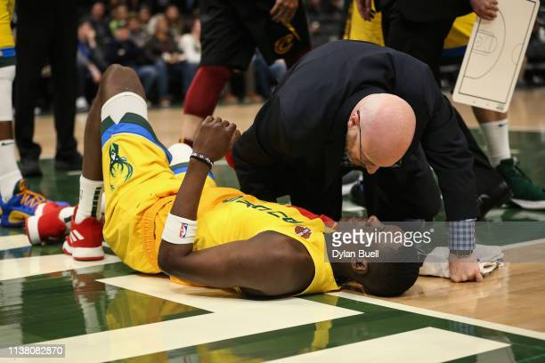 Tony Snell of the Milwaukee Bucks is attended to after being injured in the third quarter against the Cleveland Cavaliers at the Fiserv Forum on...