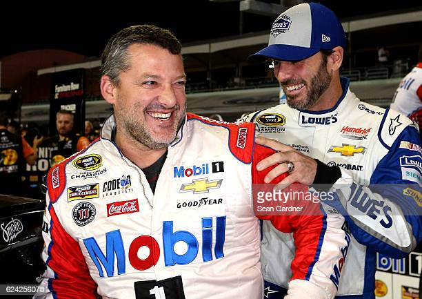 Tony Stewart driver of the Always a Racer/Mobil 1 Chevrolet and Jimmie Johnson driver of the Lowe's Chevrolet joke around on the grid during...