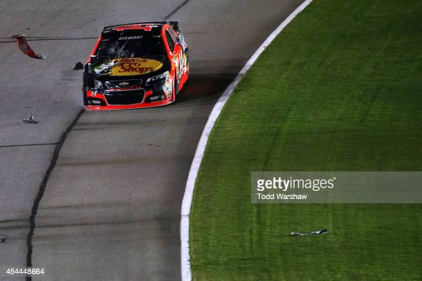 Tony Stewart driver of the Bass Pro Shops / Mobil 1 Chevrolet sheds debree on the race track after being involved in an ontrack incident during the...