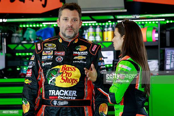Tony Stewart driver of the Bass Pro Shops/Mobil 1 Chevrolet and Danica Patrick driver of the GoDaddy Chevrolet talk in the garage area during...