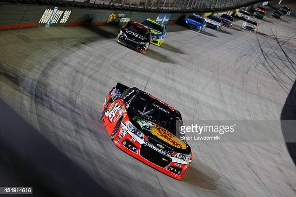 Tony Stewart driver of the Bass Pro Shops/Mobil 1 Chevrolet leads a pack of cars during the NASCAR Sprint Cup Series IRWIN Tools Night Race at...