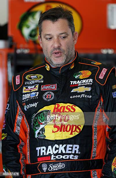 Tony Stewart driver of the Bass Pro Shops/Mobil 1 Chevrolet stands in the garage area during practice for the 57th Annual Daytona 500 at Daytona...