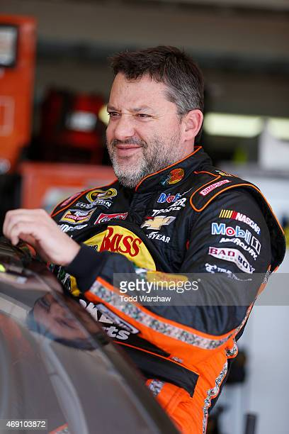 Tony Stewart driver of the Bass Pro Shops/Mobil 1 Chevrolet stands in the garage area during practice for the NASCAR Sprint Cup Series...