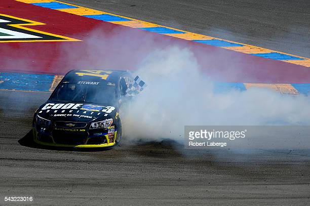 Tony Stewart driver of the Code 3 Assoc/Mobil 1 Chevrolet celebrates with a burnout after winning the NASCAR Sprint Cup Series Toyota/Save Mart 350...