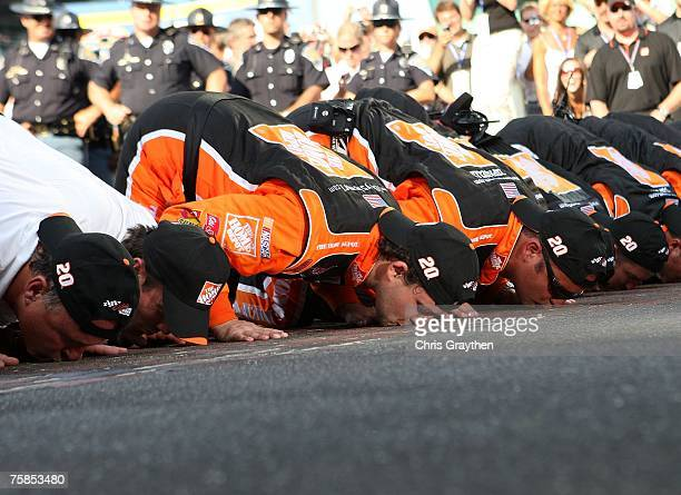 Tony Stewart driver of the Home Depot Chevrolet and crew members kiss the bricks after winning the NASCAR Nextel Cup Series 14th Allstate 400 at the...