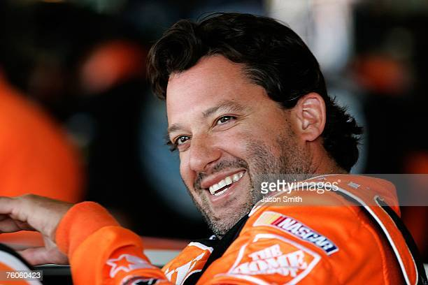 Tony Stewart driver of the Home Depot Chevrolet climbs into his car prior to practice for the NASCAR Nextel Cup Series Centurion Boats at The Glen at...