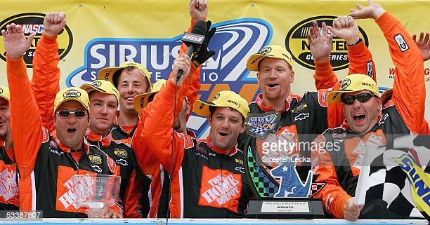 Tony Stewart driver of the Home Depot Chevrolet gestures with others after winning the NASCAR Nextel Cup Series Sirius Satellite Radio at the Glen on...